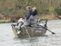 Two fisherman on the river, outboard motors are OK in this area.